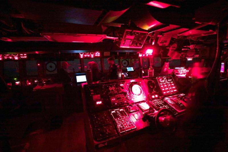 El puente iluminado en rojo de un destructor de la clase Arleigh Burke por la noche